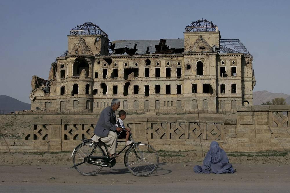 Велосипедист и женщина, просящая милостыню. На заднем плане дворец Тадж-Бек, также известный как дворец Амина. Здание было разрушено в ходе гражданской войны 1992 года.
