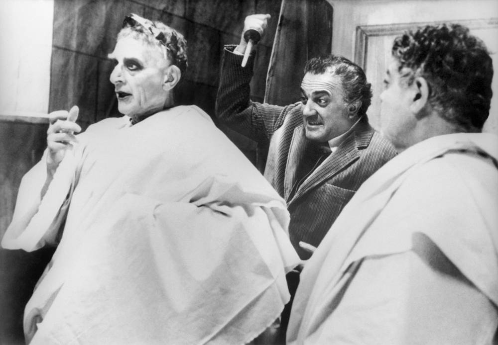 """Федерико Феллини (на втором плане) репетирует сцену с актерами на съемках фильма """"Рим"""", 1972 год"""
