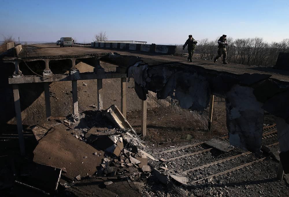 """""""Мы там вчера были около 30 минут, не было ни одного строения, которое не было бы повреждено от снарядов, ни одного здания, которое не осталось бы целым. В городе нет ни воды, ни еды, ни тепла, ни электроэнергии, ни медикаментов"""", - отметила представитель Специальной мониторинговой миссии ОБСЕ на Украине Ирина Гудыма. На фото: разрушенный автомобильный мост в Дебальцеве, 20 февраля 2015 года"""