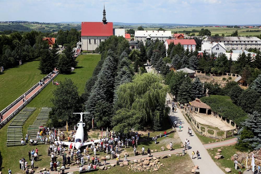 Жители польского города Кальков возле памятника в виде модели президентского самолета, установленного в память о жертвах авиакатастрофы под Смоленском, 24 июня 2012 года