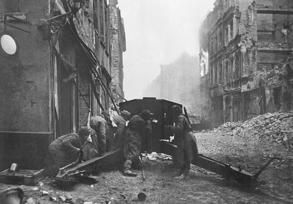 Советские артиллеристы ведут огонь по противнику на городской улице, 1945 год