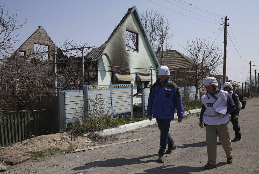 """По данным ОБСЕ, большую опасность представляет тот факт, что противоборствующие стороны в Широкине находятся очень близко друг от друга. """"В связи с этим единственным решением представляется разведение армий на достаточное расстояние"""", - подчеркнул замглавы Специальной мониторинговой миссии организации. На фото: наблюдатели ОБСЕ осматривают последствия обстрелов на улицах Широкина, 16 апреля"""