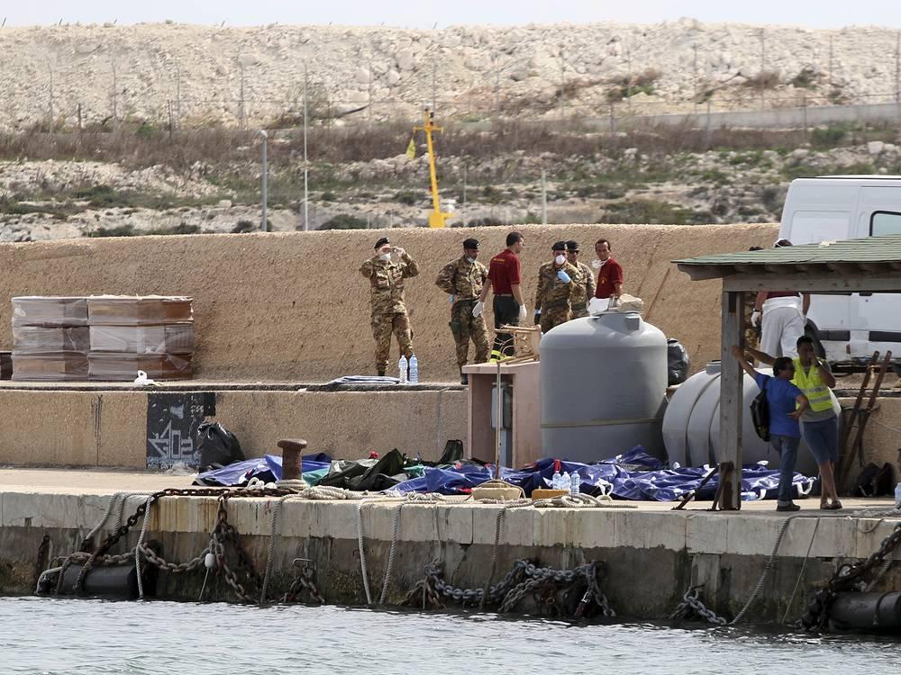 3 октября 2013 года в 120 км от Лампедузы затонуло рыбацкое судно, отправившееся от берегов Ливии и перевозившее около 500 мигрантов - преимущественно, граждан Эритреи, Сомали и Ганы. У судна отказал двигатель, из-за отсутствия средств радиосвязи экипаж зажег одеяло, чтобы подать знак бедствия, однако это вызвало сильный пожар. В результате судно затонуло, были спасены 155 человек, более 360 пропали без вести. На фото: тела утонувших иммигрантов в порту Лампедузы, 3 октября 2013 года