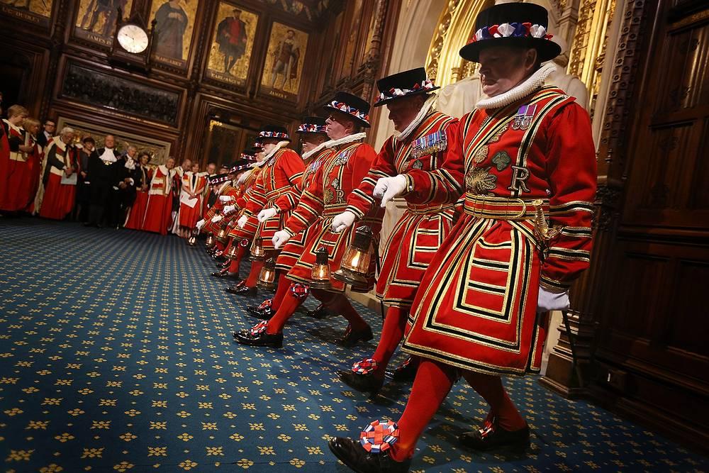 Королева приезжает в обычной одежде, в специальной гардеробной Вестминстера она переодевается в государственный наряд - в кружевное платье кремового цвета с 6-метровым шлейфом из алого бархата и мантию из горностая. На фото: церемония выступления Елизаветы II в Вестминстерском дворце, 2014 год