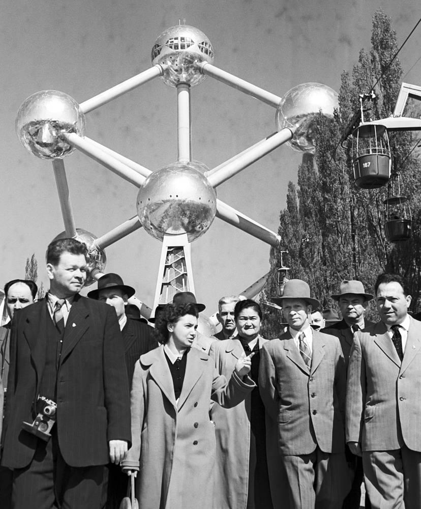 Эмблема выставки в Брюсселе - Атомиум. Это сооружение символизирует атомный век и мирное использование атомной энергии. Спроектирован архитектором Андре Ватеркейном и построен под руководством архитекторов Андре и Мишеля Полаков. До сих пор остается одной из достопримечательностей Брюсселя. На фото: советские туристы около Атомиума, 1958 г.