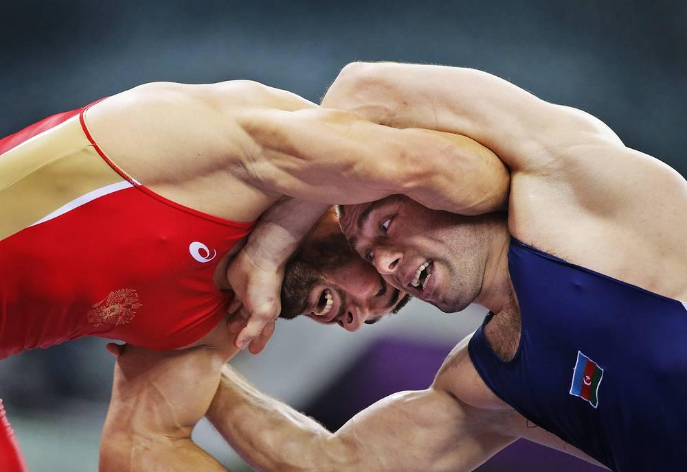 Абдусалам Гадисов (Россия, слева) и Хетаг Газюмов (Азербайджан, справа) во время полуфинальных соревнований по вольной борьбе в весовой категории до 97 кг