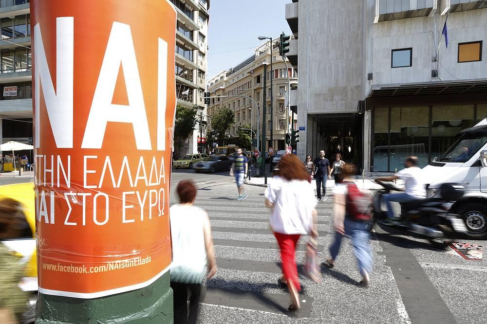 """Согласно последнему опросу, проведенному среди тысячи человек, около 47% граждан намерены проголосовать за предложения кредиторов на референдуме или считают, что они, скорее всего, так сделают. На фото: плакат с надписью """"Да"""" - Греции, """"Да"""" - евро"""" в центре Афин"""