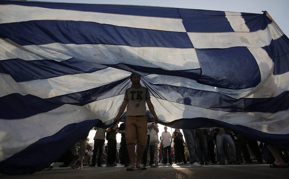 30 июня Афины не перечислили МВФ очередной платеж по кредитам на фоне провала переговоров о программе реформ. На фото: митинг в Афинах в преддверии проведения референдума по предложениям кредиторов