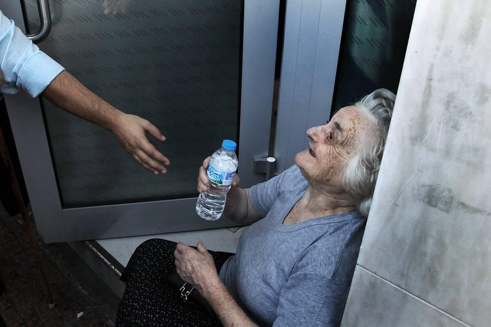 Вкладчики Греции только в последние две недели вывели со счетов местных банков почти €8 млрд, сообщила газета Financial Times. На фото: греческая пенсионерка в очереди за пенсионными накоплениями