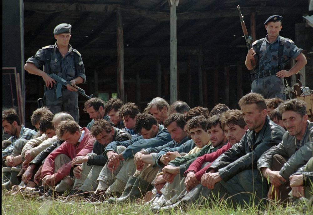 По разным данным, были убиты от 6 до 8 тыс. человек, включая гражданских лиц, пытавшихся покинуть город. Среди убитых было порядка 500 подростков, не достигших 18 лет. На фото: два сербских полицейских охраняют группу боснийских мусульман из Сребреницы. 5 августа 1995 года