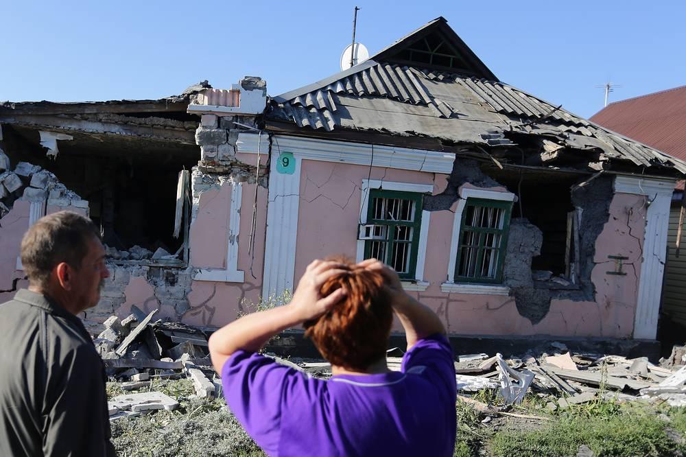 В  результате обстрела пострадал газопровод, были обесточены некоторые дома. На фото: жители города у разрушенного дома после обстрела на одной из улиц города