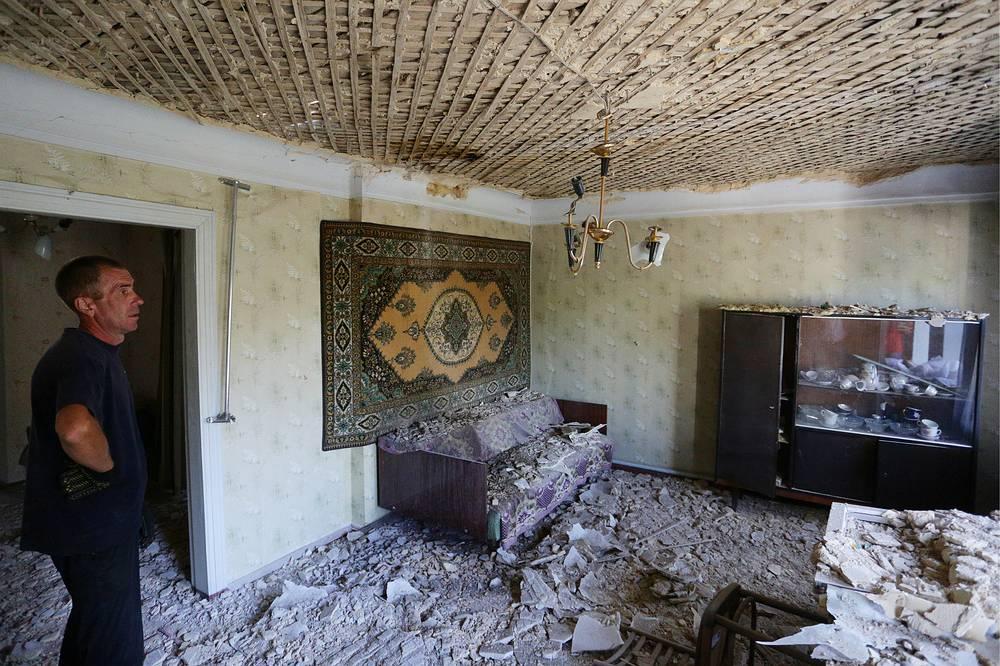"""""""Режим тишины"""" в Донбассе официально вступил в силу 15 февраля. Требование прекратить огонь было заложено в комплексе мер по реализации минских соглашений.  На фото: житель города в разрушенном доме после обстрела на одной из улиц города"""