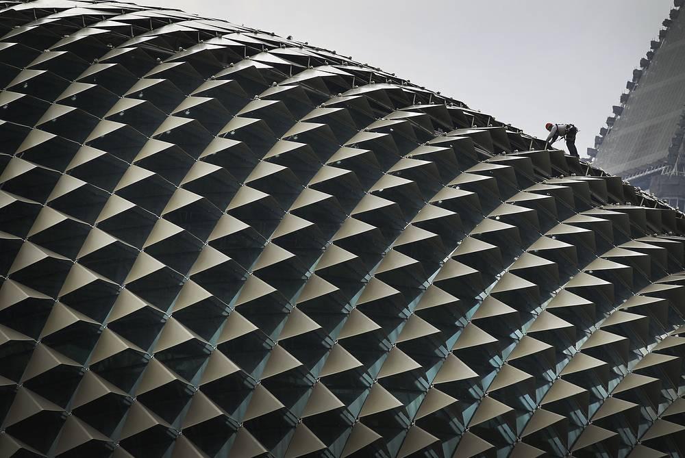 Чистота на улицах Сингапура - результат строжайших законов в сфере утилизации мусора и хорошей работы коммунальных служб. На фото: рабочий осуществляет рутинную уборку