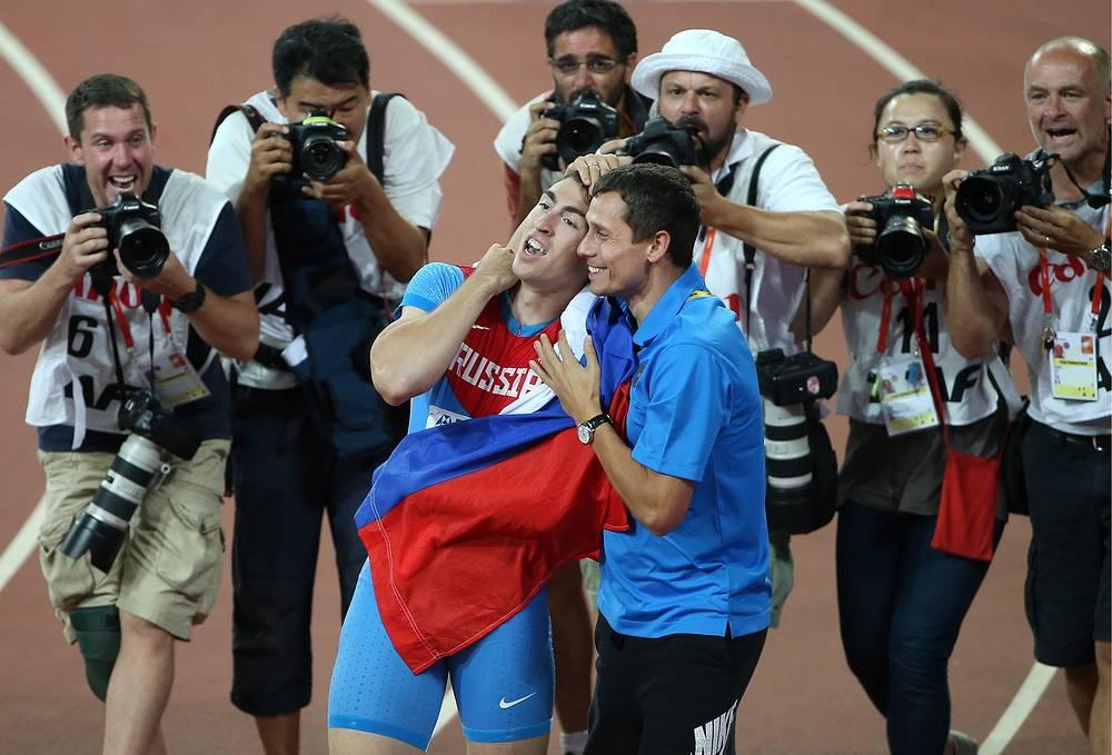 Российский спортсмен Сергей Шубенков, завоевавший золотую медаль, и главный тренер сборной России по легкой атлетике Юрий Борзаковский (в центре слева направо) после финиша в финальном забеге на 110 м с барьерами среди мужчин на чемпионате мира по легкой атлетике в Пекине, 28 августа