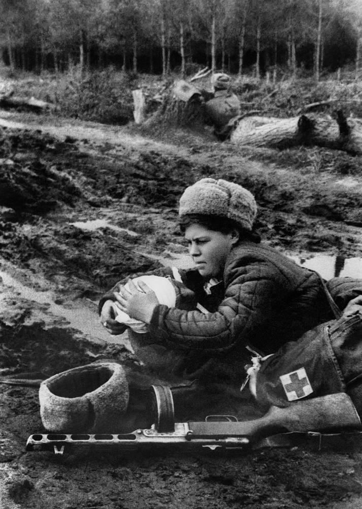 Первая помощь на поле боя. Медсестра делает перевязку раненому бойцу, 1943 год