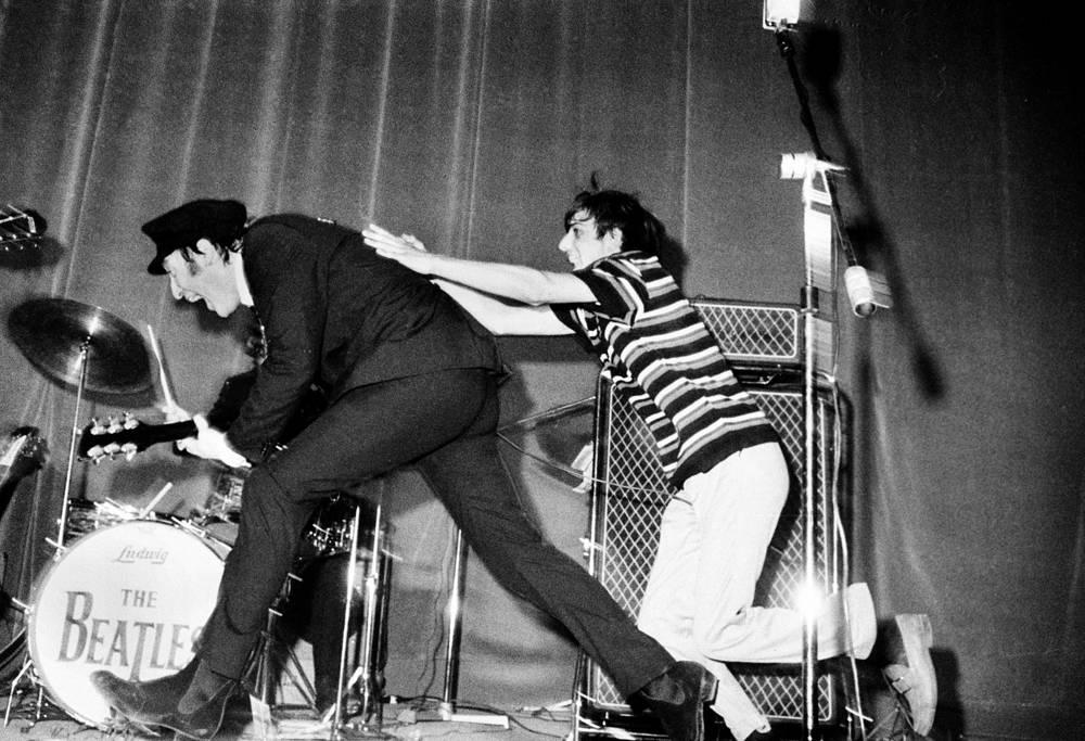 Во время концерта в Лондоне один из фанатов попытался отобрать у Леннона головной убор, 1965 г.