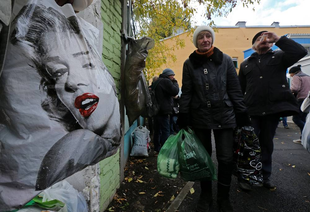 """Бездомные в уличном магазине, где можно бесплатно подобрать теплые вещи и получить модный совет от стилистов, во дворе благотворительной организации """"Ночлежка"""" в Санкт-Петербурге, 9 октября"""