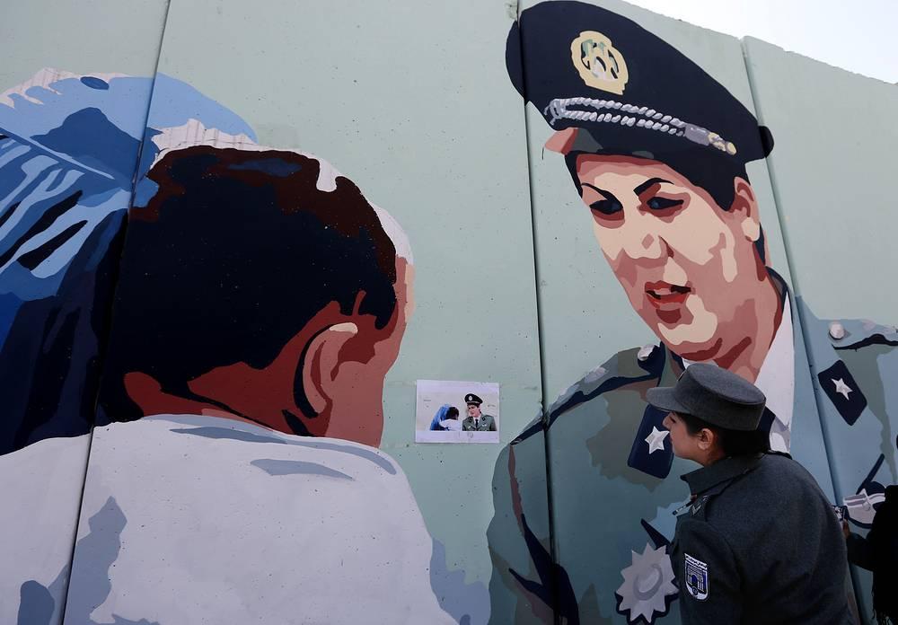 Афганская женщина-полицейский Фриба Хамид напротив стены с ее портретом в Кабуле