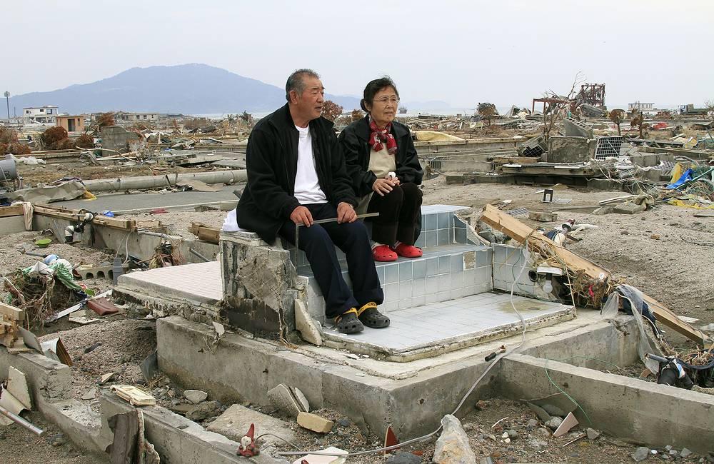 Тейцо Терасака (70) и его жена Кейко (68) на развалинах своего дома в опустошенном цунами городе Рикудзентаката, префектура Иватэ, северная Япония, 01 мая 2011 года