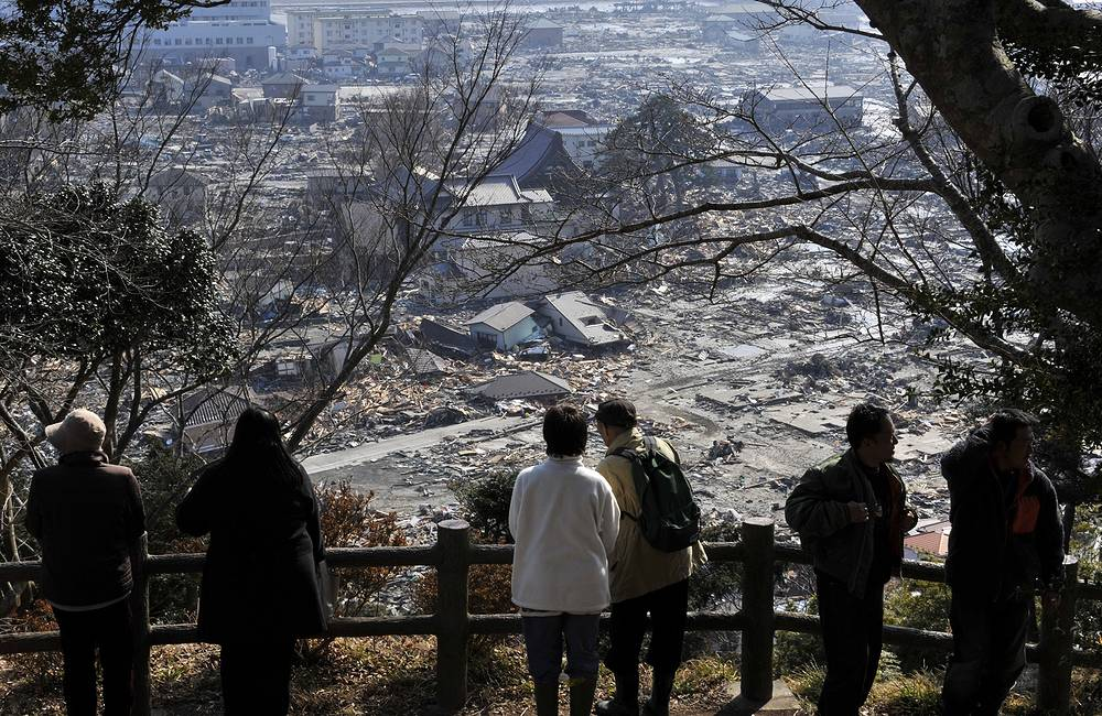 Выжившие после цунами смотрят на разрушенную область Исиномаки, префектура Мияги, около 270 км к северу от Токио, северная Япония, 13 марта 2011 года