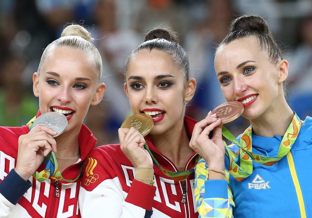 Яна Кудрявцева (серебро), олимпийская чемпионка Маргарита Мамун и украинская спортсменка Анна Ризатдинова (бронзовая медаль) (слева направо) во время церемонии награждения