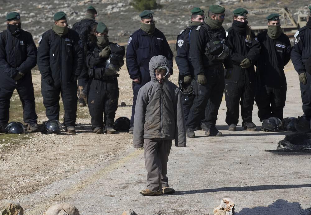 Ребенок стоит рядом с израильскими полицейскими во время эвакуации из нелегального поселения