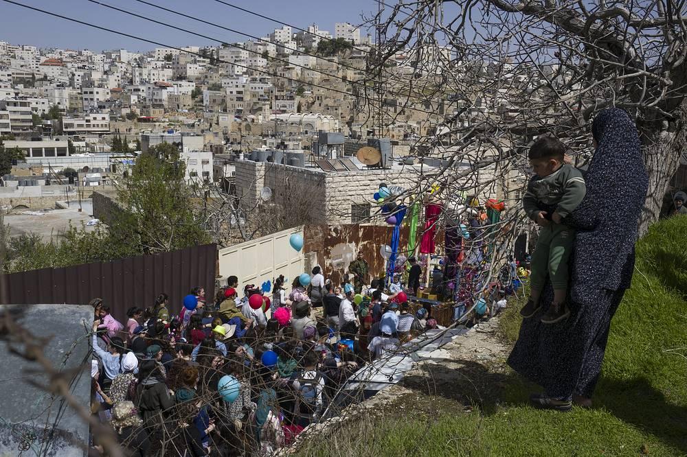 Палестинка с сыном наблюдает за парадом в честь Пурима на Западном берегу реки Иордан