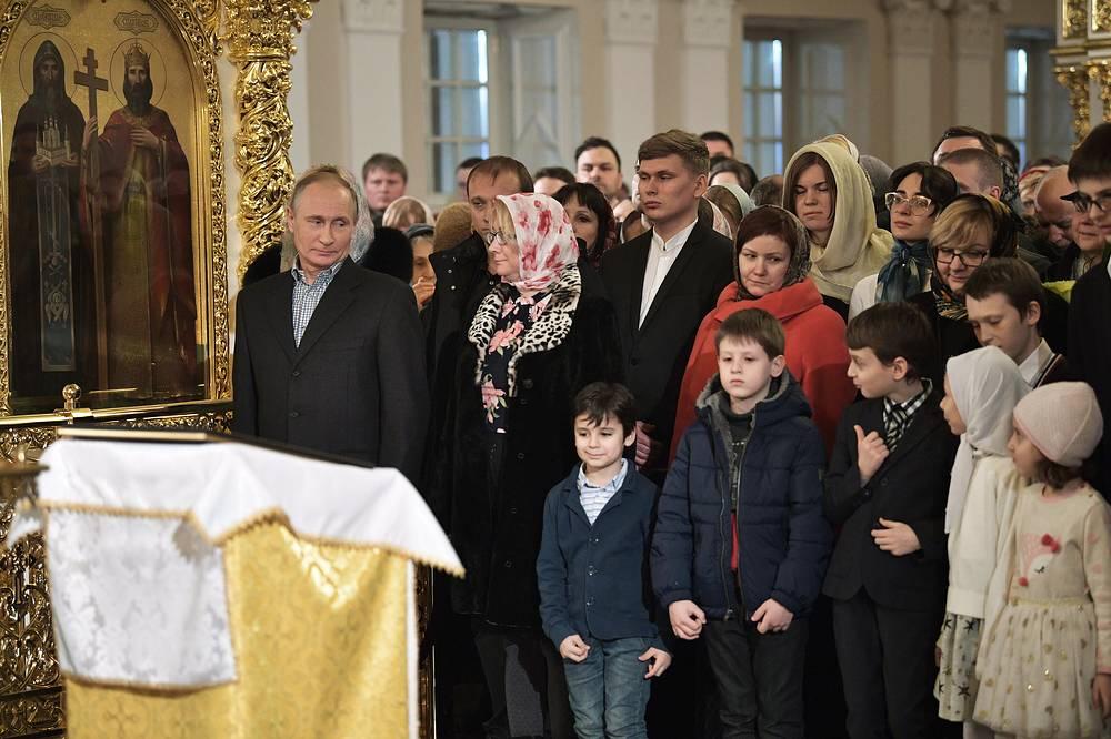 Санкт-Петербург. Президент РФ Владимир Путин с верующими во время праздничного богослужения по случаю Рождества Христова в церкви Симеона и Анны