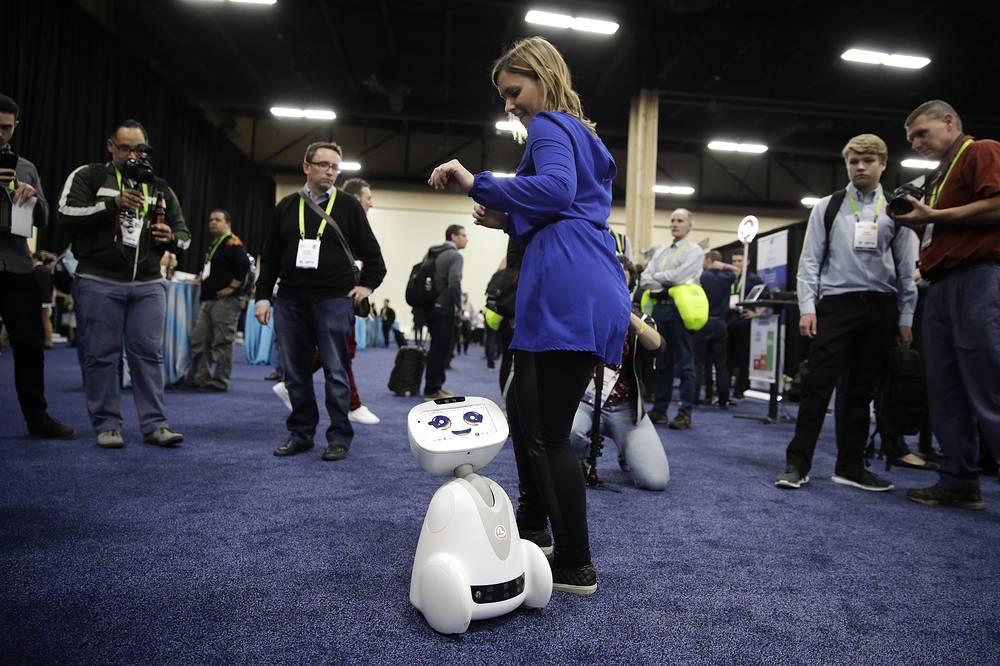 Участница выставки танцует с роботом Buddy