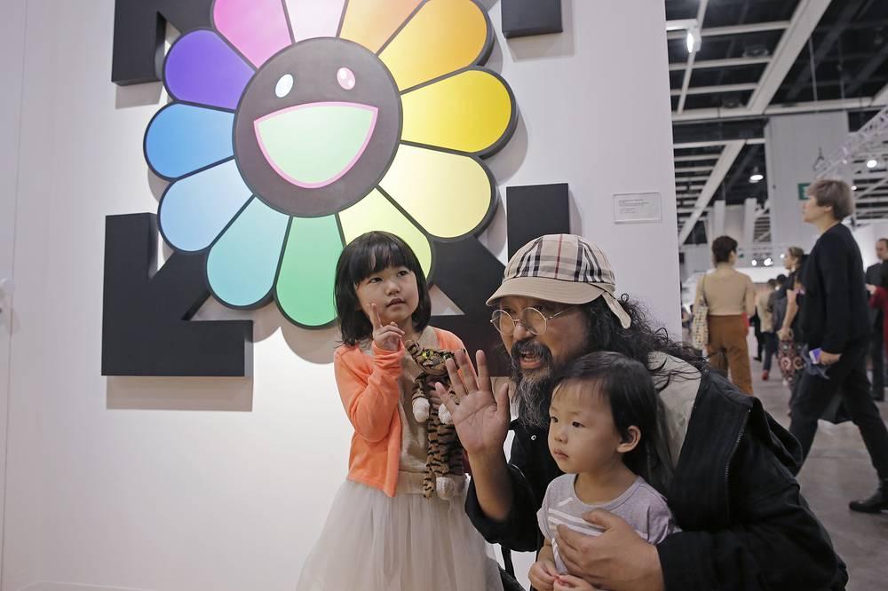 Японский художник Такеши Мураками позирует с фанатами на фоне своих работ