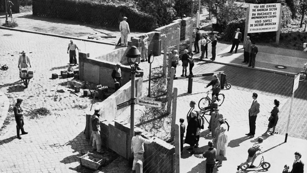 Жители западного Берлина (справа) наблюдают за  возведением стены, 1961 год