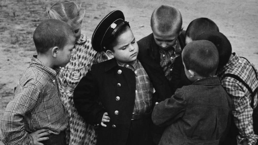 Первоклассник хвастается новой формой, 1955. Фото ИТАР-ТАСС. В 1948 году вновь ввели обязательную школьную форму, похожую на военные мундиры.