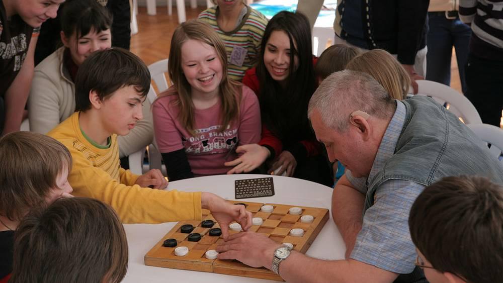 Александр Суворов играет в шашки с детьми.  Фото ИТАР-ТАСС/Сергей Шахиджанян