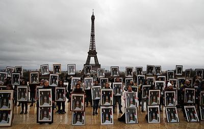 Экоактивисты устроили в Париже акцию протеста с перевернутыми портретами Макрона