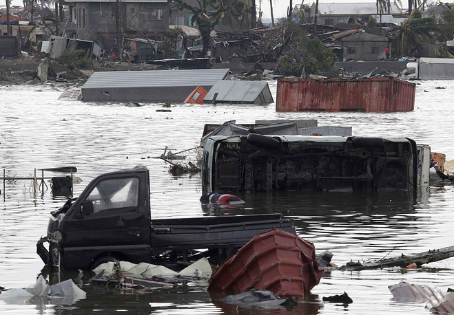 Cars and debris from damaged houses float along a river in Tacloban city, Leyte province central Philippines on Sunday, November 10, 2013.