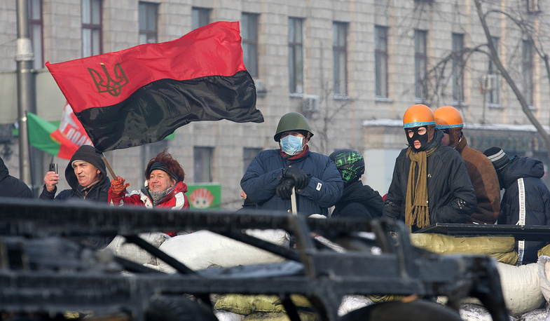 Protesters stand on a barricade during another day of anti-government protest in Kiev