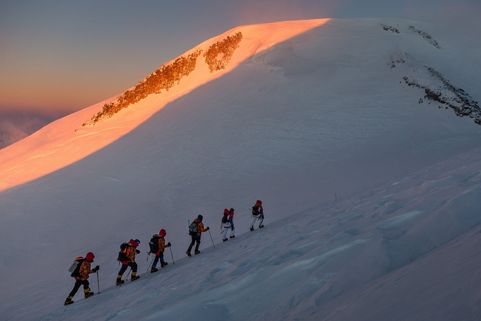 mountain climbers ascent the summit of Mt. Elbrus to light the Olympic Flame during the Olympic torch relay in Kabardino-Balkaria province, southern Russia