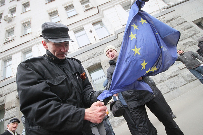 A protester trying to set fire to a European Union flag