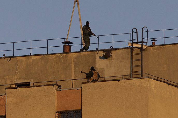 Armed men on the roof of the military unit where the shooting took place