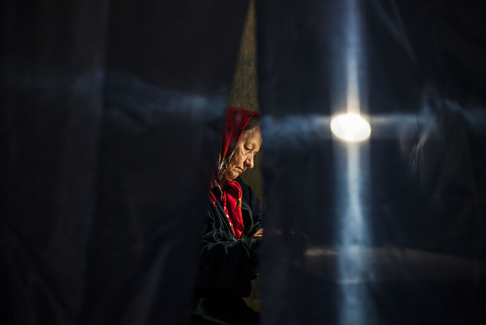 A Ukranian woman casts her vote in a booth at a polling station in the center of Donetsk