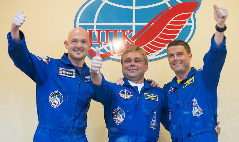 Flight Engineer Alexander Gerst of the ESA (left) Soyuz Commander Maxim Surayev of the Russian Federal Space Agency Roscosmos (center) and Flight Engineer Reid Wiseman of NASA
