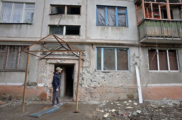 A local looks at the wall of his house damaged in a shelling attack