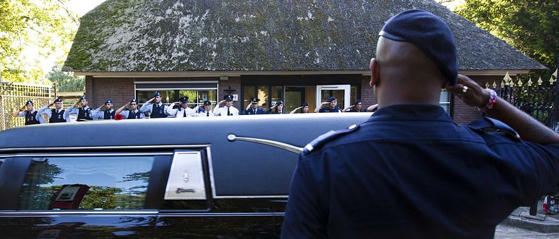 A soldier salutes as the convoy of funeral hearses passes