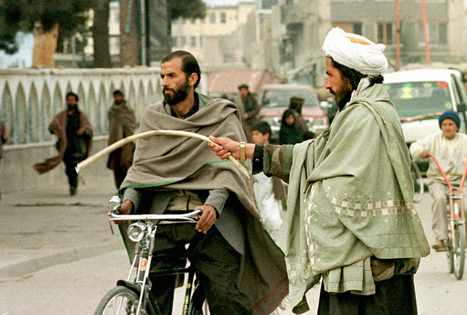 In 1996, Kabul was seized by the fighters of the Taliban movement which established the Islamic Emirate of Afghanistan. Photo: a Taliban soldier instructs a bypasser to go to pray in a mosque in Kabul, 1996