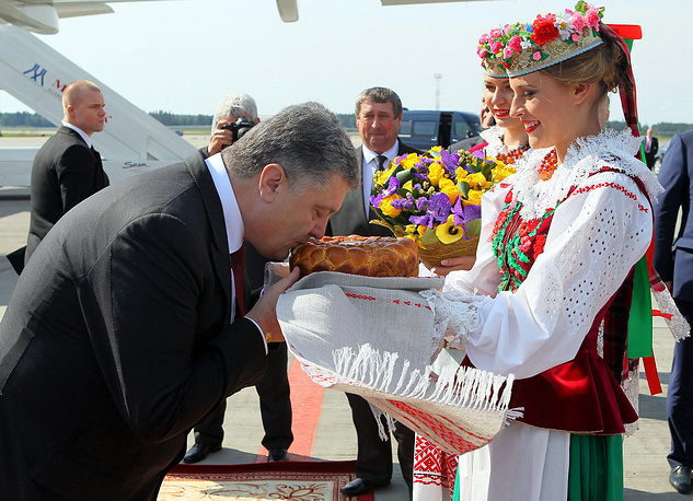 Ukraine's President Petro Poroshenko (L) kisses bread and salt held by a Belarussian woman dressed in national costume, as he arrived at the National airport Minsk
