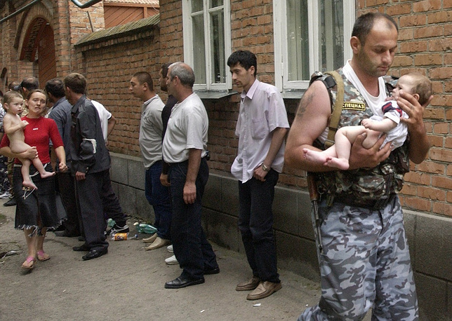 A special ops soldier carries a six-month-old baby released by the terrorists