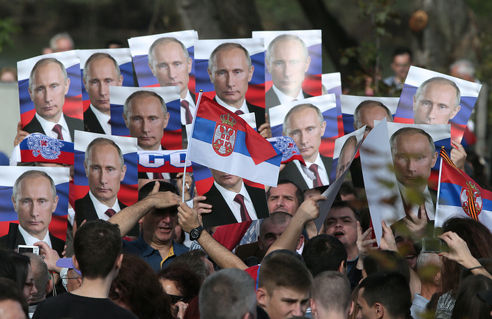 People hold portraits of Vladimir Putin at a military parade in Belgrade, 16 October 2014