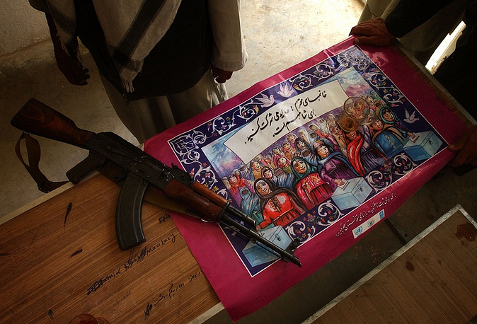 Photo: Kalashnikov assault rifle lies on a poster that promotes Afghan participation at the gate of a voter registration office in Khwaja Omri, Afghanistan, 2004