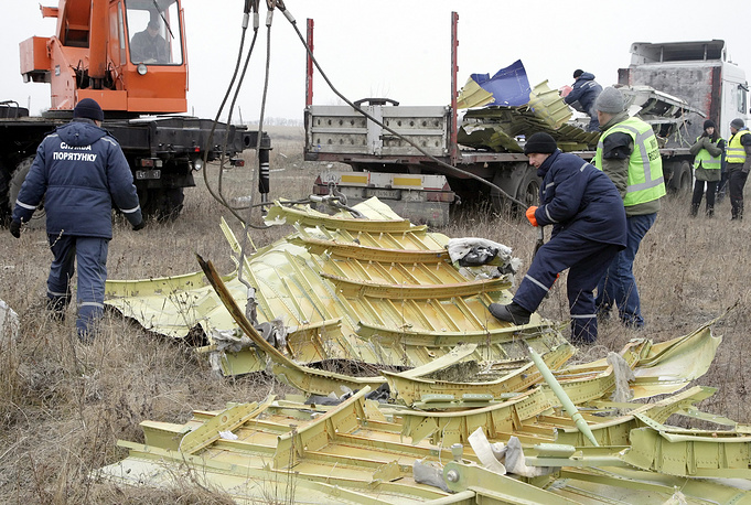 Workers and Dutch experts remove parts of the wreckage of Malaysia Airlines passenger jet MH17 at the crash site in Grabovo village, about 70 km from Donetsk, Ukraine, 18 November 2014