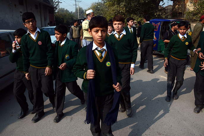 Photo: School children rescued by the security forces leave following an attack in Peshawar